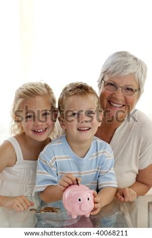Smiling grandmother and children saving money in a piggybank - stock photo