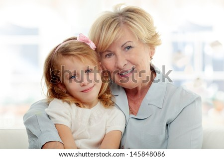 Smiling grandmother embracing her granddaughter - stock photo
