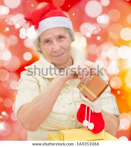 smiling grandmother in Santa cap with a Christmas gifts - stock photo