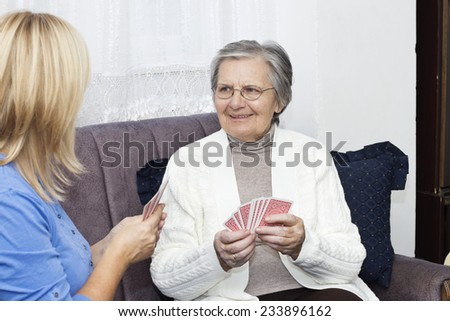 Smiling grandmother playing cards with mature nurse. - stock photo