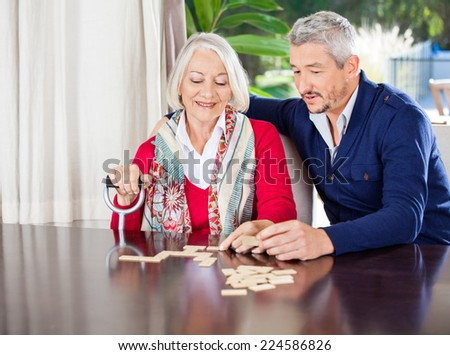 Smiling grandmother playing dominoes with grandson at nursing home - stock photo