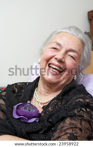 Smiling grandmother with silk violet rose - stock photo