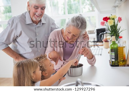 Smiling grandparents helping children to cook in the kitchen