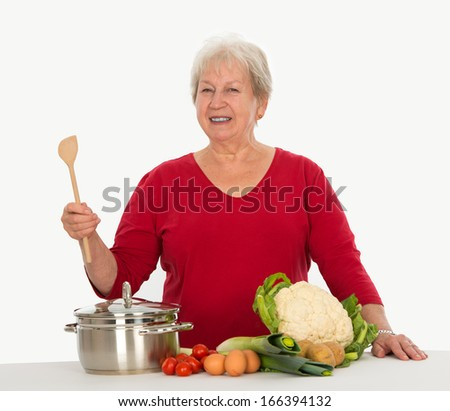 smiling gray-haired woman is cooking - stock photo