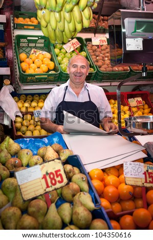 Smiling greengrocer at the market stall - stock photo
