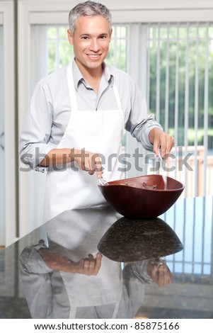 Smiling grey hair man tossing salad in apron - stock photo
