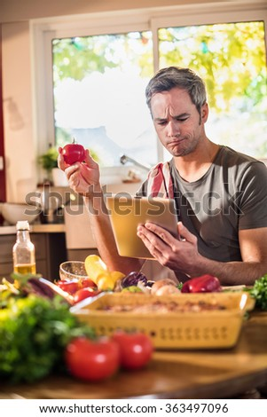 Smiling grey haired man sitting at a wooden kitchen table full of colorful fresh vegetables, looking at recipes on a tablet. He is smiling, wearing casual clothes. Blurred background