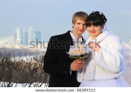 smiling groom and bride holding bouquet of roses and look at camera at winter outdoors - stock photo