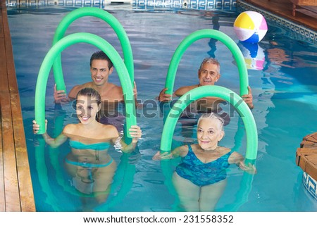 Smiling group doing aqua fitness class together in a swimming pool - stock photo