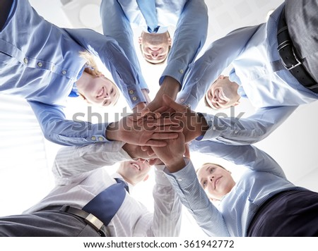 smiling group of businesspeople standing in circle - stock photo