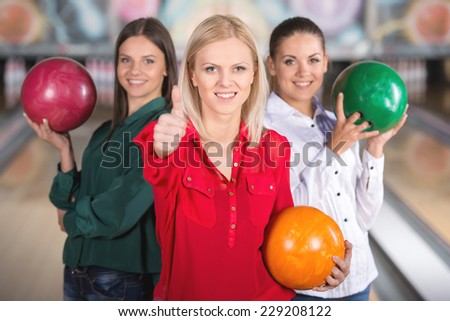 Smiling group of female friends bowling and are holding balls and looking at the camera.