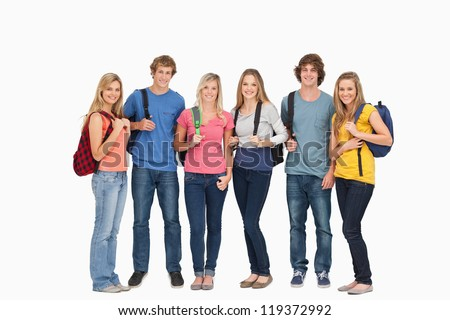 Smiling group with backpacks on as they smile and look at the camera - stock photo