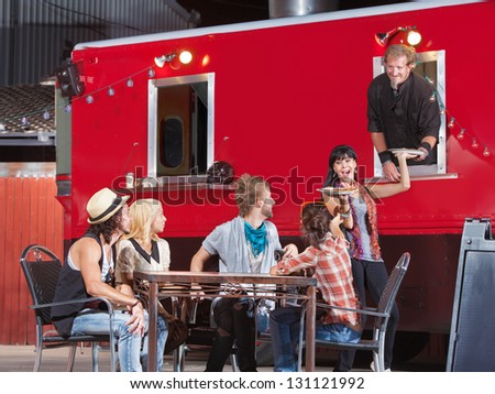 Smiling group with pizza orders from food truck - stock photo