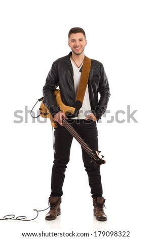 Smiling guitarist in black leather jacket stands with bass guitar. Full length studio shot isolated on white. - stock photo
