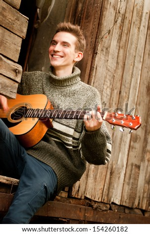 Smiling guitarist played by guitar in lost village - stock photo