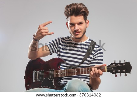 smiling guitarist seated in studio background with guitar on lap while showing rock and roll sign - stock photo