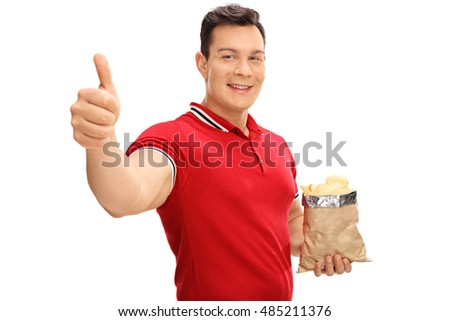 Smiling guy holding a bag of potato chips and giving a thumb up isolated on white background