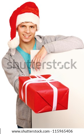Smiling guy in santa hat with gift box and blank billboard isolated on white - stock photo