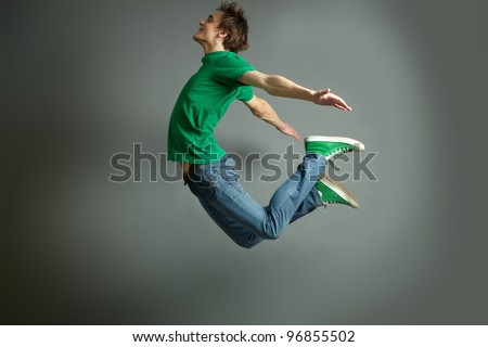 Smiling guy jumping high holding hands behind - stock photo