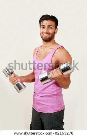 Smiling gym trainer with dumbbells