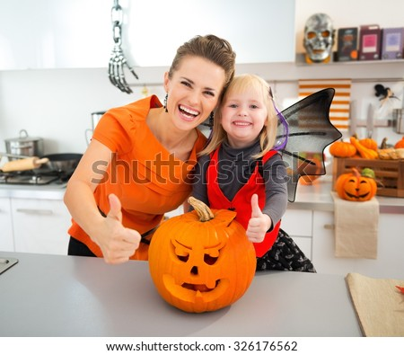 Smiling halloween dressed girl with mother standing in decorated kitchen near big orange pumpkin Jack-O-Lantern and showing thumbs up. Traditional autumn holiday - stock photo