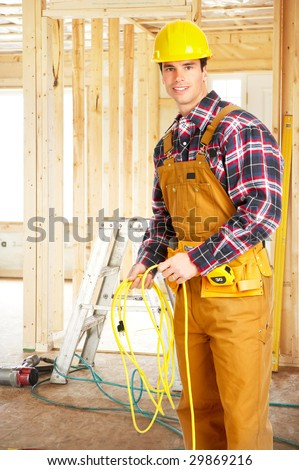 Smiling handsome builder in yellow uniform. - stock photo