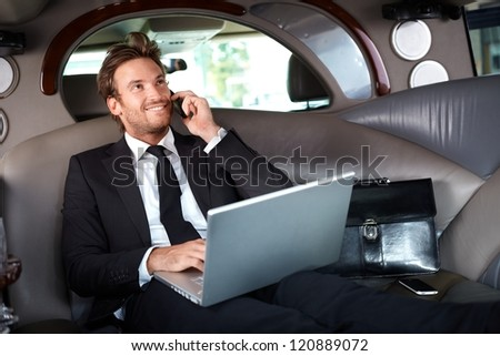 Smiling handsome businessman sitting in luxury limousine, working on laptop computer, smiling. - stock photo