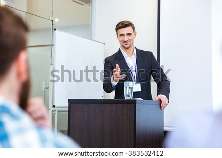 Smiling handsome businessman standing at tribune in conference hall and pointing in audience - stock photo