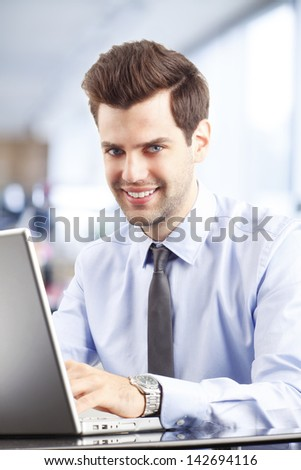 Smiling handsome businessman using laptop in office