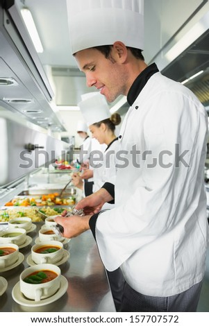 Smiling handsome chef seasoning his soup standing in the kitchen - stock photo