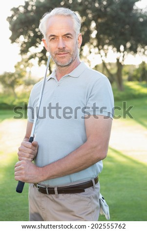 Smiling handsome golfer looking at camera on a sunny day at the golf course - stock photo