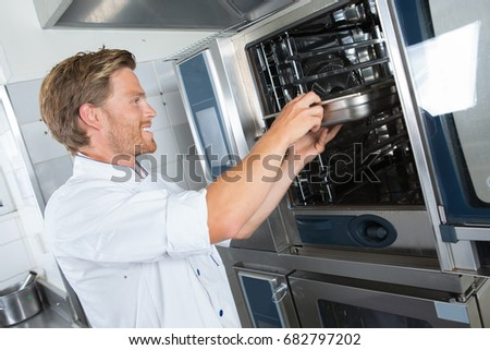 smiling handsome male cook holding dish in the restaurant kitchen