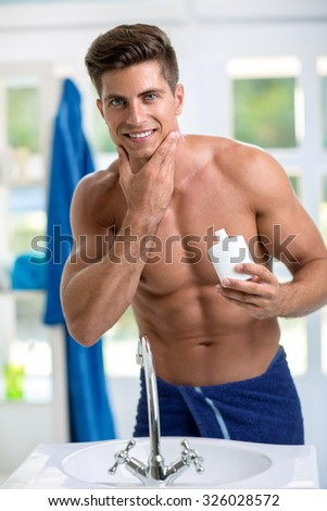 Smiling handsome  man applying after shave on skin of  beard - stock photo