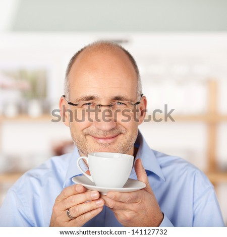 Smiling handsome man holding a cup of coffee - stock photo