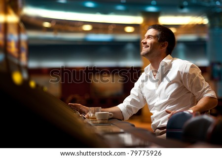 smiling handsome man hoping to win at slot machine - stock photo