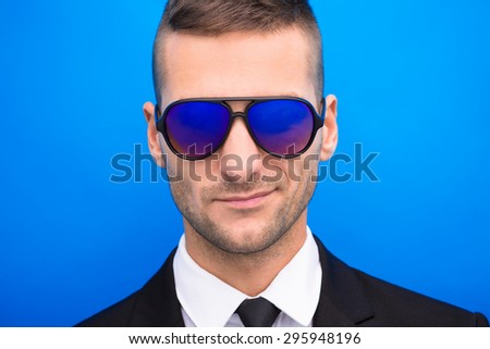 Smiling handsome man in black business suit on blue background. Man in fashionable sunglasses posing for photographer. - stock photo