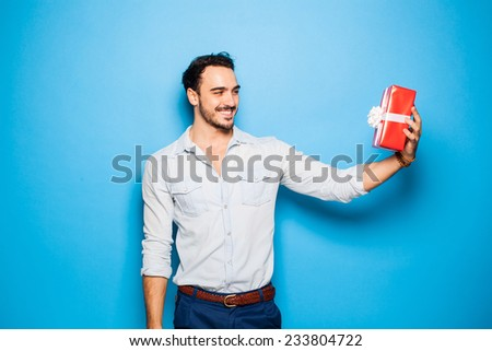 smiling handsome man looking happy at his christmas gift, on blue background - stock photo