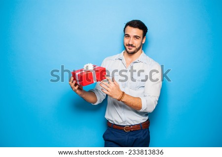 smiling handsome man presenting a red christmas gift, on blue background - stock photo