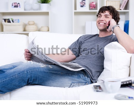 Smiling handsome man with phone and newspaper - lying at home