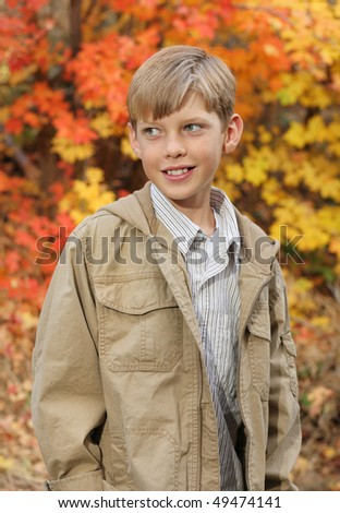 smiling handsome preteen standing outdoors in fall colors - stock photo