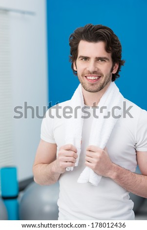 Smiling handsome unshaven yong man at the gym standing holding onto a towel around his neck with Pilates balls in the background - stock photo