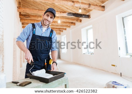 Smiling handsome young builder using paint roller while working indoors - stock photo