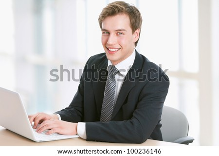 Smiling handsome young business man working on laptop - stock photo