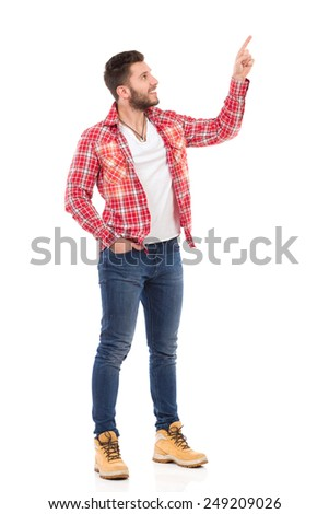 Smiling handsome young man in jeans and lumberjack shirt standing and pointing up. Full length studio shot isolated on white. - stock photo