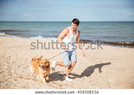 Smiling handsome young man jogging with his dog on the beach - stock photo