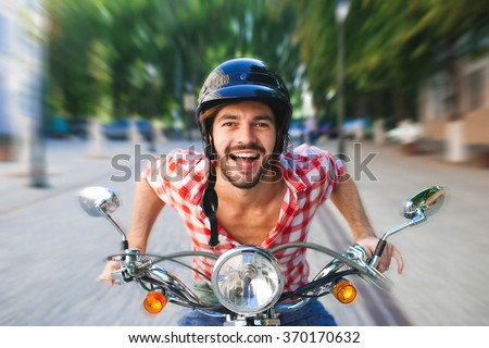 Smiling handsome young man riding white scooter. Motion blurred concept. - stock photo