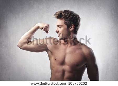 Smiling handsome young man showing his biceps - stock photo