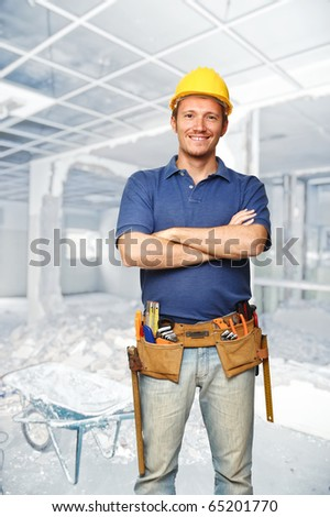 smiling handyman and construction site background - stock photo