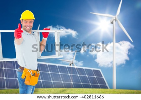 Smiling handyman carrying ladder while gesturing thumbs up against large solar panel and three wind turbines - stock photo