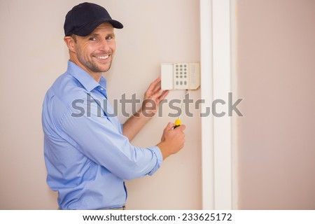 Smiling handyman fixing an alarm system on the wall - stock photo